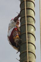 One of the voladores climbs the pole.
