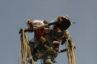 The Tezcatlipoca Voladores wind their ropes around the pole.